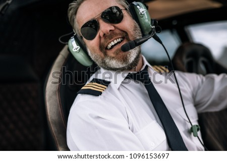 Confident pilot with headset smiling in the private helicopter. Happy mature male helicopter pilot sitting in cockpit.