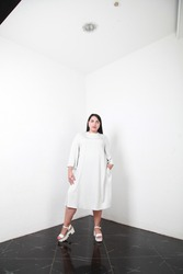 Confident plus size model in loose white dress posing in simple interior over white walls background for fashion campaign. Concept of body positivism and diversity. White Caucasian brunette female