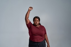 Confident plus size young african american woman in casual clothes looking at camera, standing with fist raised isolated over gray background. Social issues, protest concept. Front view