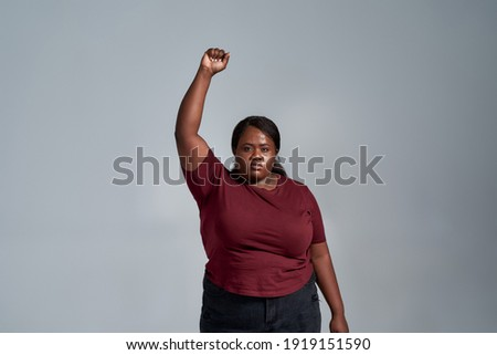 Confident plus size young african american woman in casual clothes looking at camera, standing with fist raised isolated over gray background. Social issues, protest concept. Front view Stock photo ©