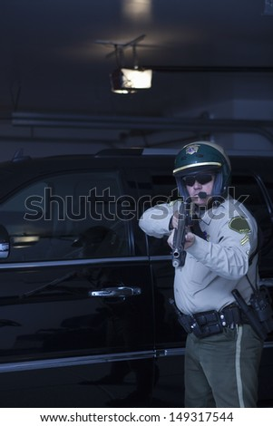 Confident policeman aiming handgun while standing in front of car
