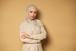 Confident portrait of serene and successful beautiful arab Muslim woman posing with crossed arms on beige background with copy space. Islamic fashion. Beige background with copy space.