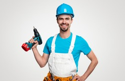 Confident positive repairman in blue shirt and hardhat and white overall with toolkit on waist and electric screwdriver smiling and looking at camera, against white background