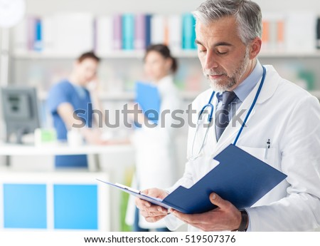 Confident professional doctor in the office checking patient\'s medical records on a clipboard, medical staff working on the background