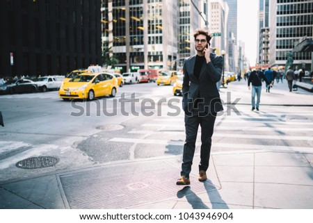 Confident proud CEO strolling on New York street and talking with business partner on smartphone discussing last financial news.Successful economist in stylish formal wear communicating on telephone