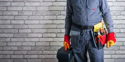 Confident repairman in uniform with toolbox. Banner.