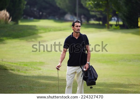 Confident rich man at golf game standing on beautiful green golf course holding bag and golf ball, handsome rich man at his favorite hobby, male golf player at the course with a club sack