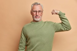 Confident satisfied grey haired man raises arm and shows muscle demonstrates results after regular training in gym wears spectacles and jumper isolated over brown background being proud of himself