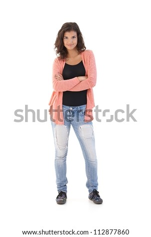 Confident schoolgirl standing arms crossed, looking at camera, smiling.