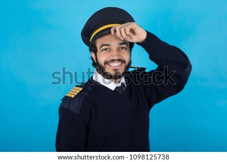 Confident security man wearing the uniform touches the cap he wears on a blue background. #1098125738