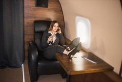 Confident self assured young businesswoman sitting in private plane with her feet on table, talking on mobile phone, holding glass of champagne, wearing formal black suit, high heel shoes.