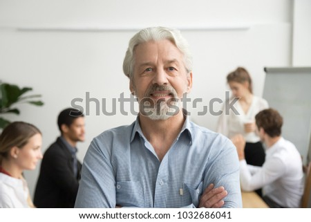 Confident senior businessman leader looking at camera with team at background, smiling aged company boss posing in office with arms crossed, older mentor or executive professional head shot portrait