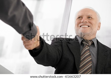 Confident senior businessman shaking hands in office, smiling.?