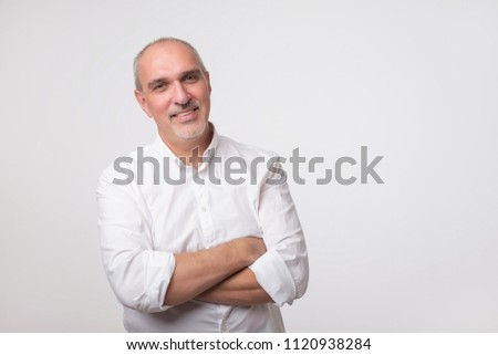 Confident senior man in white t-shirt crossing hands on chest and looking at camera while standing against gray background. Self confident hispanic senior.