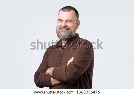 Confident senior man with beard in brown t-shirt crossing hands on chest and looking at camera. Self confident european guy. #1368936476