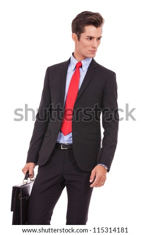 confident serious business man looking to his side while holding a suitcase