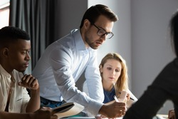Confident serious male ceo executive manager in glasses analyzing financial paper documents at briefing meeting with young diverse colleagues or developing company growth strategy together in office.