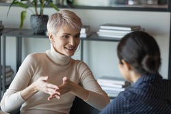 Confident short-haired businesswoman talk with client during formal meeting in office. HR manager applicant interaction at job interview communication. Two diverse mates discuss common project concept
