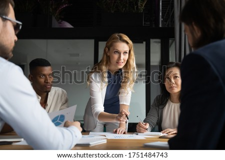 Confident skilled businesswoman explain marketing data paper report financial results analysis to multi-ethnic colleagues, company staff gathered at meeting brainstorming thinking strategizing concept