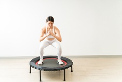 Confident slim fit female doing squats on mini trampoline during high intensity interval training at yoga studio