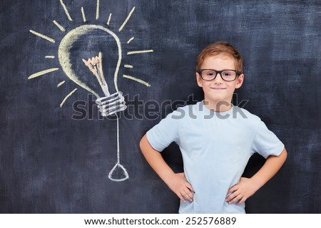 Confident smart pupil standing against blackboard with bulb idea sign