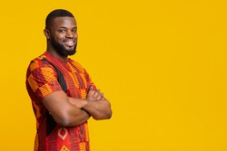 Confident smiling african american guy in bright traditional t-shirt over yellow studio background, copy space