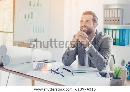 Confident smiling architect in formal wear dreaming and  working with blueprint papers and drawings in modern lightful office