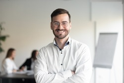 Confident smiling business man professional coach wear glasses stand arms crossed looking at camera, happy male executive company owner corporate manager leader in office, headshot close up portrait