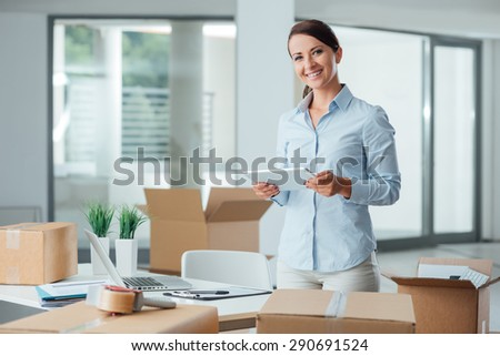 Confident smiling business woman moving in her new office, she is unpacking boxes and using a digital tablet