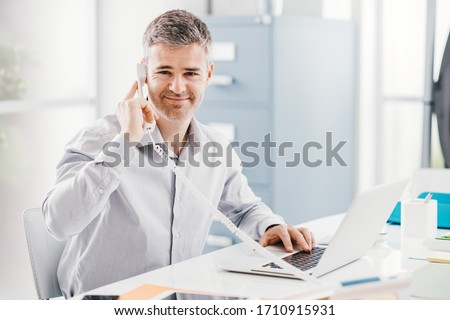 Confident smiling businessman and consultant working in his office, he is having a phone call: communication and business concept