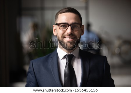 Confident smiling businessman executive wear suit glasses looking at camera, happy proud professional ceo leader male company owner manager posing in office, close up head shot business portrait