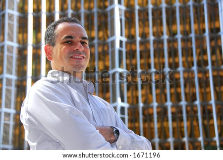 Confident smiling businessman with crossed arms, success concept