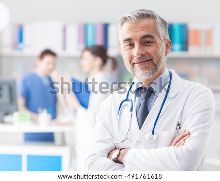 Confident smiling doctor posing and looking at camera with arms crossed, medical staff working on the background #491761618