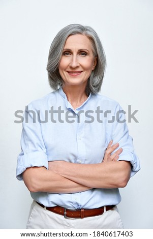 Confident smiling mature business woman standing arms crossed isolated on white background. Older senior businesswoman, 60s grey-haired lady executive leader coach looking at camera, vertical portrait