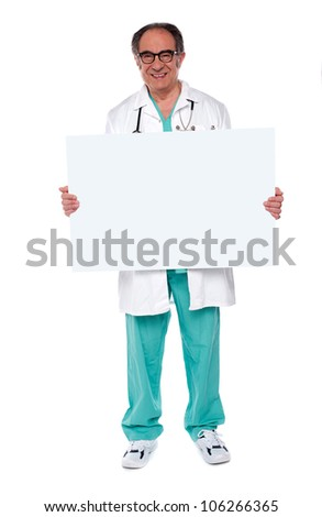 Confident smiling senior doctor showing blank whiteboard. Isolated