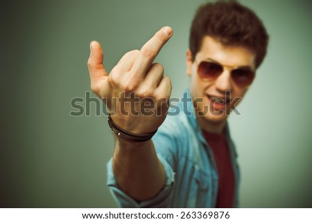 Confident smiling teenager in sunglasses showing middle finger