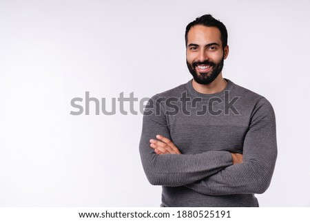 Confident smiling young arabian man in casual clothes isolated over white background