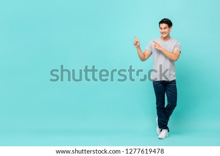Confident smiling young Asian man pointing hands to copy space aside studio shot isolated on light blue bakground