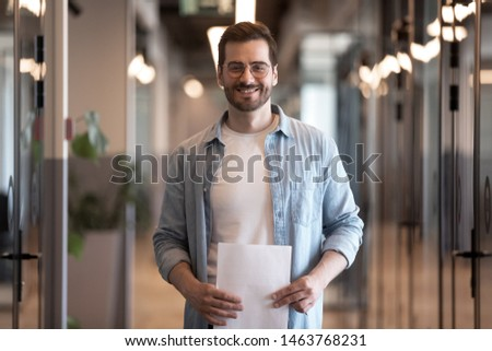 Confident smiling young business man looking at camera standing in modern office hallway, happy positive millennial male professional worker holding papers posing in modern office, portrait