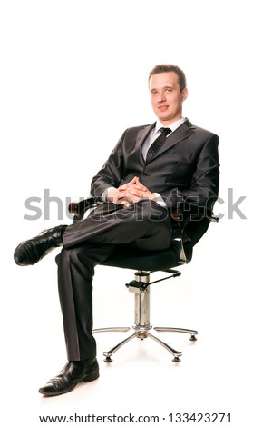 Confident smiling young businessman sitting on a chair isolated on white