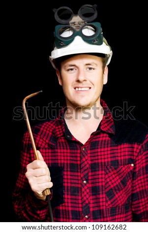 Confident smiling young panel beater wearing a safety helmet and goggles and holding an welding torch in hand on a black studio background