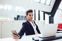 Confident smirking young man in formal suit relaxing from work checking social media using mobile in modern office looking at camera