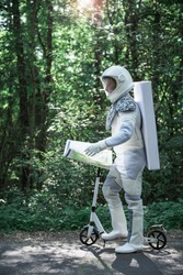 Confident spaceman wearing white armor is standing near scooter and holding map. He looking forward. Profile