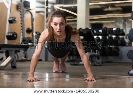 Confident sporty woman performing pushups on floor at health club