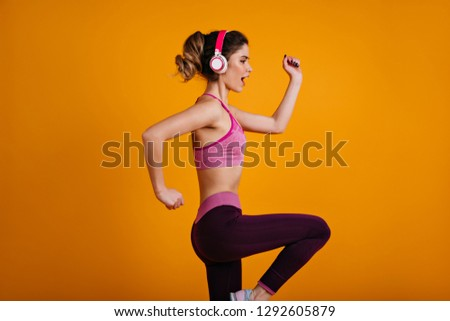 Confident sporty woman training in headphones. Portrait of fit girl running on yellow background.