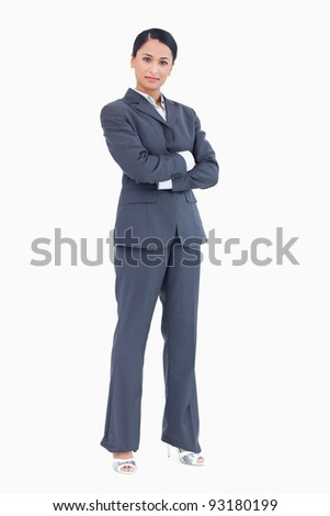 Confident standing businesswoman with arms folded against a white background