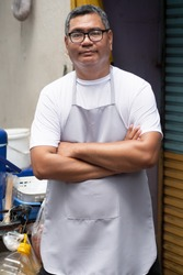 confident street hawker man working with his delicious meatball skewer street food; concept of asian street food, tourism with local food, small business, street food hawker