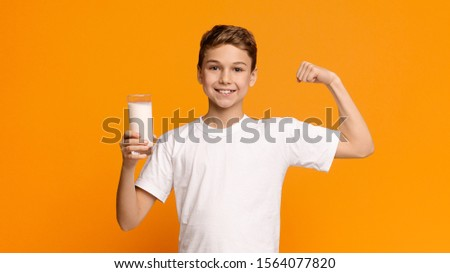 Confident strong teenager enjoying milk and showing his biceps, orange panorama background