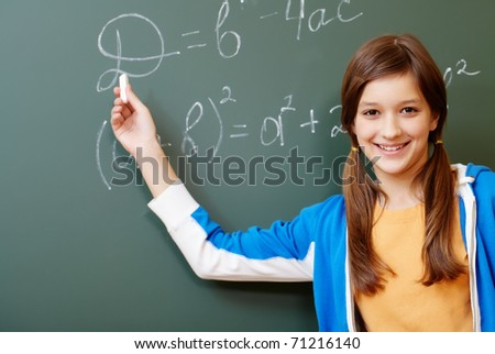 Confident student pointing at formula on blackboard during algebra lesson