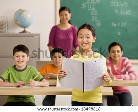 Confident student reads her report in school classroom